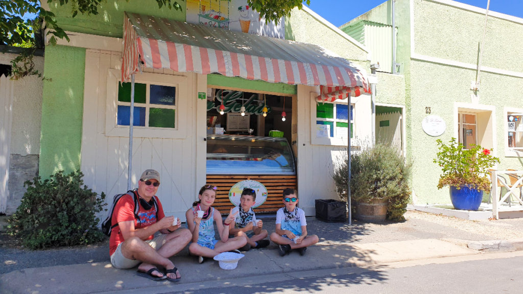 Dad and 3 kids sitting on curb enjoying ice cream in front of Don Gelato in Stanford village