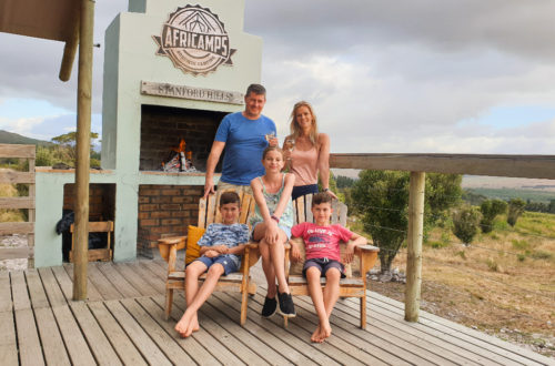 One Stop Wanderlust Family sitting on the deck at AfriCamps Stanford Hills